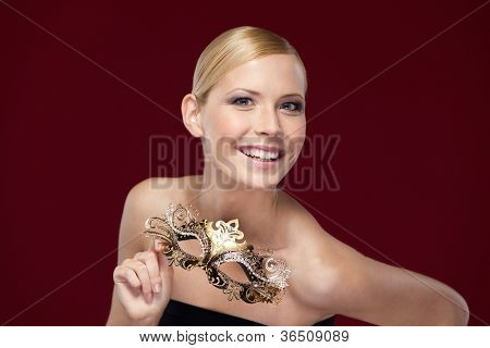 Pretty woman with patterned masquerade mask, isolated on purple