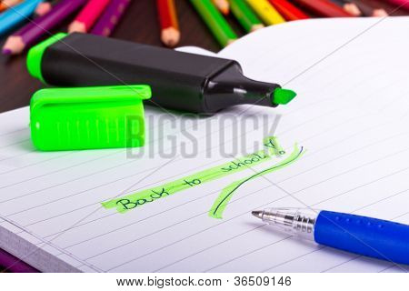Back to school sign in notebook with pencils in background