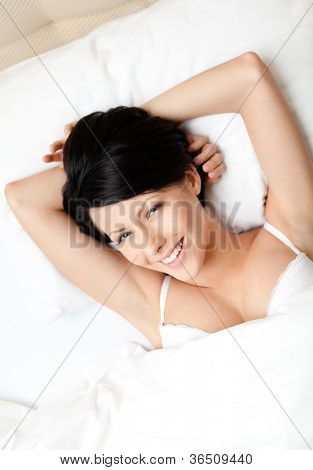 Sleeping woman in the bed with white bed linen, white background