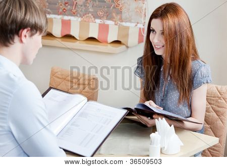 Couple keeps the menu to make an order at the cafe