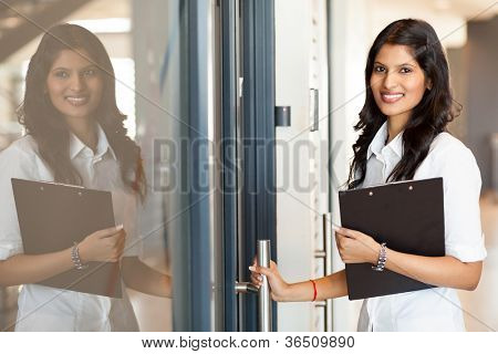 beautiful young indian white collar worker opening office door
