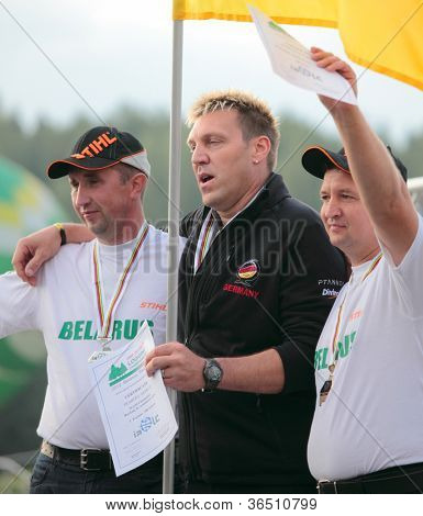RAUBICHI, BELARUS - AUGUST 25: German M. Trabert (center), Belarussians A. Andron (left) and V. Durovich with medals on World Logging Championship in Raubichi, Minsk region, Belarus at August 25, 2012
