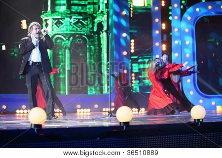 MOSCOW - DEC 17: Aleksey Glizin sings on scene with big display, dancers during concert of Legend RetroFM in Sports complex Olimpiyskiy, on Dec 17, 2011 in Moscow, Russia.