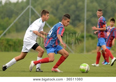 KAPOSVAR, HUNGARY - SEPTEMBER 1: Unidentified players in action at the Hungarian National Championship under 16 game between Kaposvar(green) and Videoton (blue) September 1, 2012 in Kaposvar, Hungary.