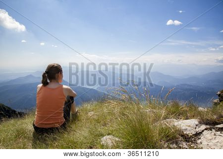 Woman sitting on mountain top of Monte Generoso admiring mountain landscape around Lugano lake and blue sky.