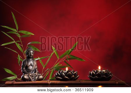 Buddha in meditation with burning candle and bamboo leaf on red background.