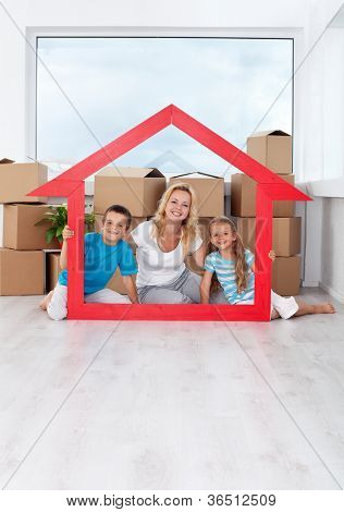 Happy family in their new home laughing by a large house shaped frame