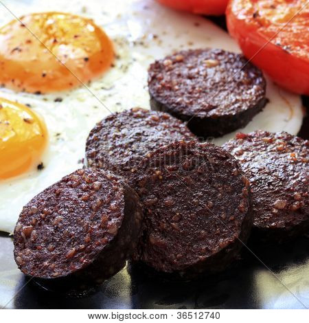 Breakfast of traditional black pudding, fried eggs and tomatoes.
