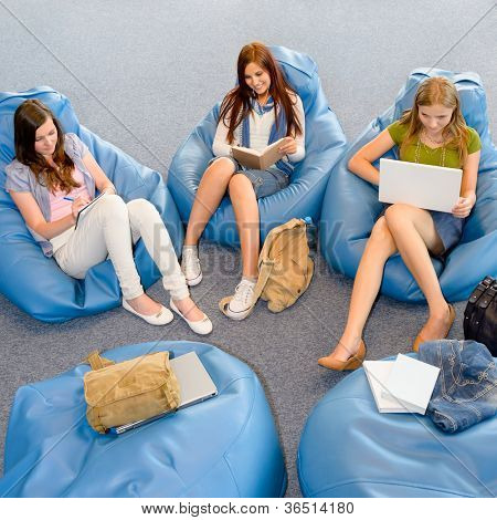 Young student girls resting on blue beanbags at library