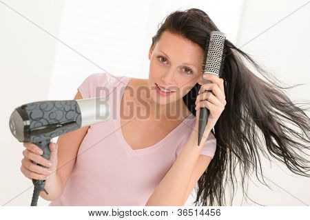 Brunette woman blow-drying long hair using round hairbrush