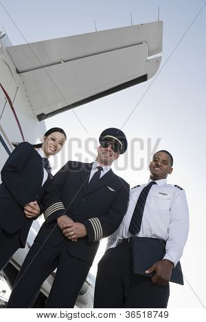 Low angle view of three multiethnic cabin crew members standing together against airplane wing at airfield