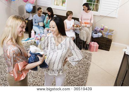 Schwangere Frau und Freund, die Abhaltung von Babykleidung auf ein Baby-Dusche