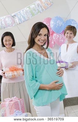 Porträt von glücklichen schwangeren mit Freunden halten Geschenke auf einer Baby-Dusche