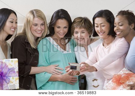 Happy pregnant woman with friends taking self-portrait  at a baby shower