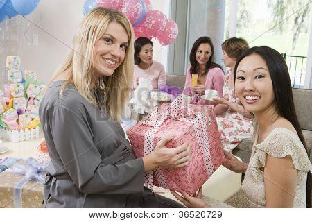 Schwangere Frau auf einer Baby-Dusche mit Geschenken und Freunde
