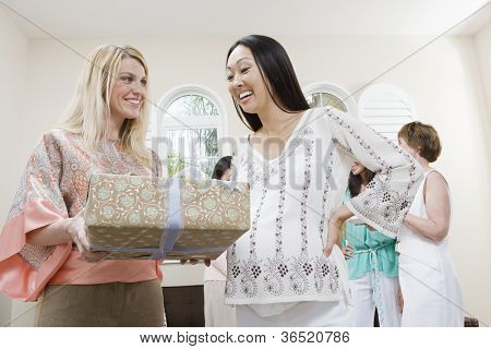 Happy pregnant woman with female friend at a baby shower