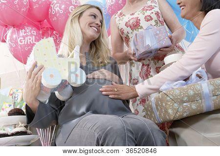 Freundin berühren Bauch einer schwangeren Frau auf einer Baby-Dusche