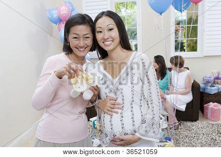 Porträt von middle aged Woman mit pregnant Woman holding Baby Booties und Spielzeug auf einer Baby-Dusche