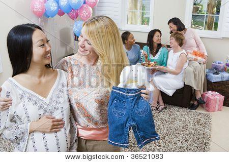 Glückliche schwangere Frau und Freund, die Abhaltung von Babykleidung auf ein Baby-Dusche