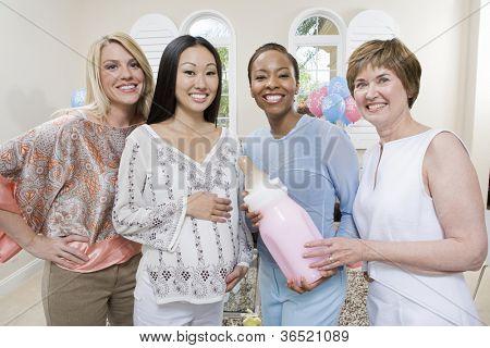 Porträt von glücklichen schwangeren mit Freunden halten große Babyflasche
