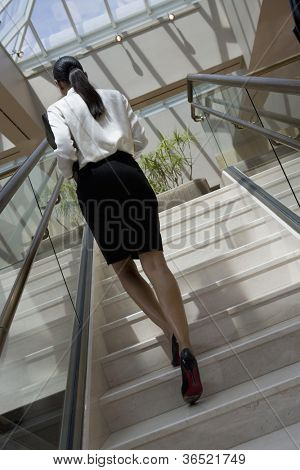 Rear view of an African American business woman moving up staircase