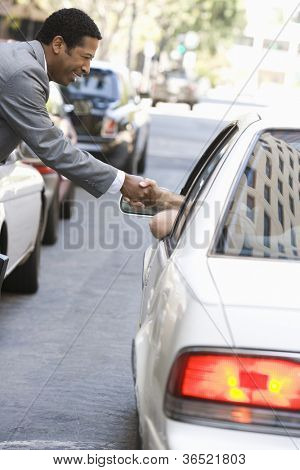 Side view of businessman shaking hand with a person in a car