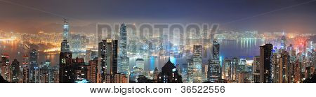 Hong Kong city skyline panorama at night with Victoria Harbor and skyscrapers illuminated by lights over water viewed from mountain top.