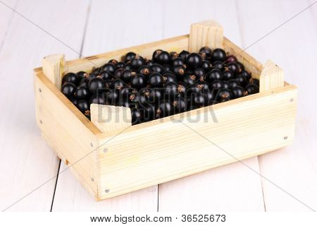 Black currant in crate on wooden background