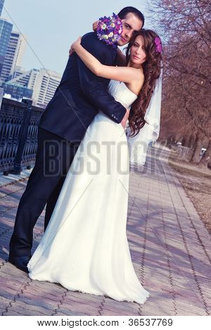Young wedding couple on city background. Camera angle view.