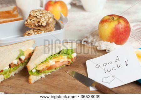 Lunchbox am Frühstückstisch mit einer viel Glück-Meldung