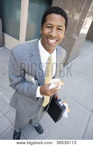 High angle view of happy African American business man eating sandwich