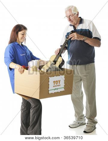 "A young teen holding a large box with a holiday ""Toy Donations"" sign as an elderly man is donating a toy guitar.  Focus on girl,  On a white background."