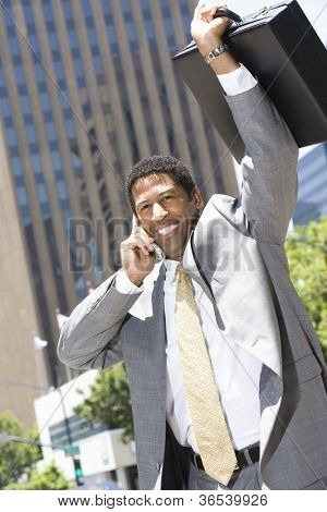 An African American businessman sharing his victory while communicating on mobile phone