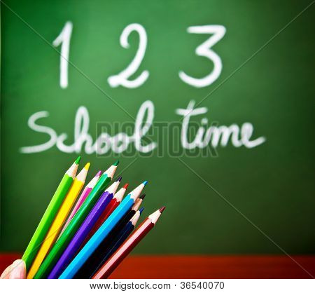 "Image of colorful pencils and green chalkboard with selective focus, multi colors crayons in preschool, handwriting phrase ""school time"" on blackboard in classroom, education and knowledge concept"