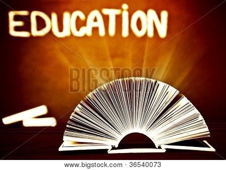 Image of open book on wooden school desk in classroom, textbook over brown chalkboard, magic book with glowing light, back to school, knowledge and education concept, retro style photo