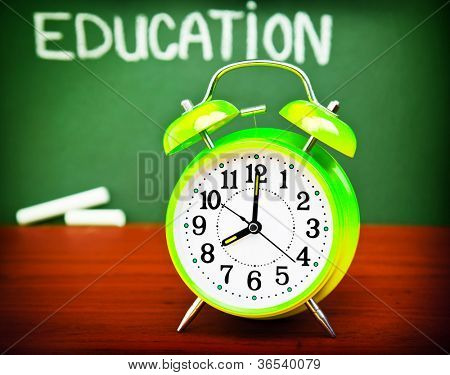 "Photo of alarm clock on wooden desk in classroom, handwriting word ""education"" on green blackboard, autumn season, yellow watch in school class, back to school, knowledge concept"