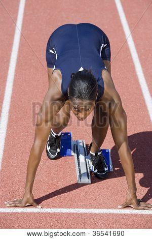 African American female runner in start up position
