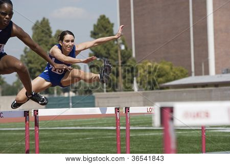Female athletes clearing hurdles in race