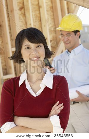 Portrait of an Asian woman smiling with foreman standing in background at construction site