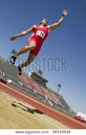 Full length of a male athlete doing a long jump into a sandpit