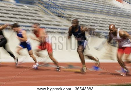 Blurred motion of male athletes racing in stadium