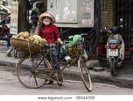 Female Street Vendor Selling Pineapples Out Of A Basket On Her Bicycle.