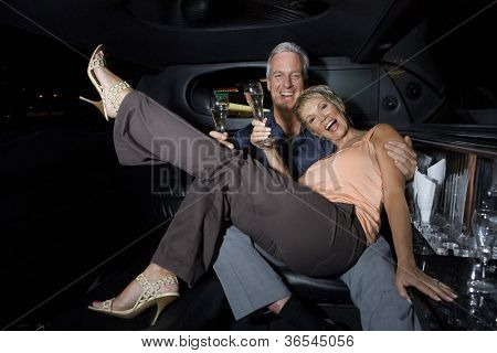 Senior couple toasting in a limousine