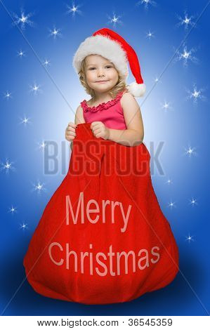 Little cute girl dressed in santa clause costume in big Christmas bag