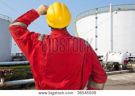 Oil engineer looking at overdue maintenance and safety issues of storage tanks with crude oil supply