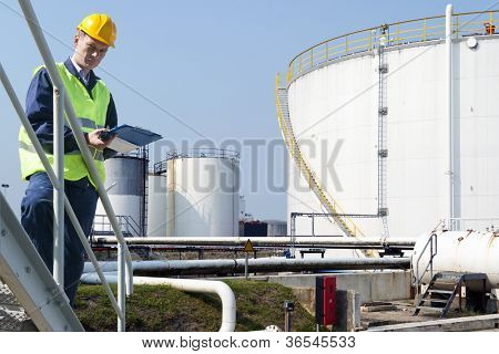Engineer with a clipboard taking notes of the quality and state of oil silos of a petrochemical industry for safety reasons