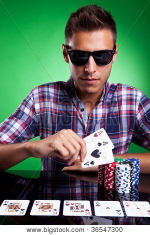 portrait of a young casual man with sunglasses showing his pair of aces, over green background