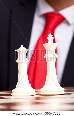 White chess king and queen in front of business man in suit