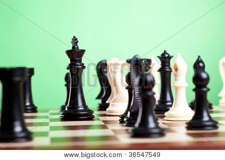 Chess pieces on board. Focus on the black king. Green background.