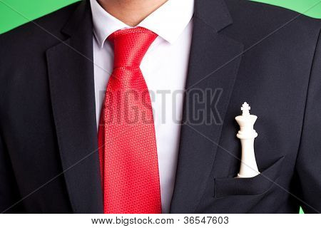Business man holding a white chess king in his pocket. green background
